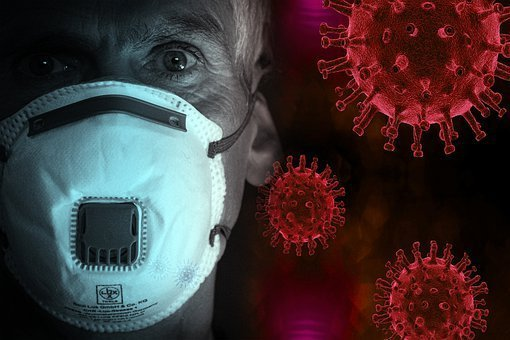 A closeup of a man with a mask on next to virus cells.
