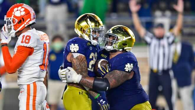 Two Notre Dame players embrace as they defeat Clemson in a close football game.