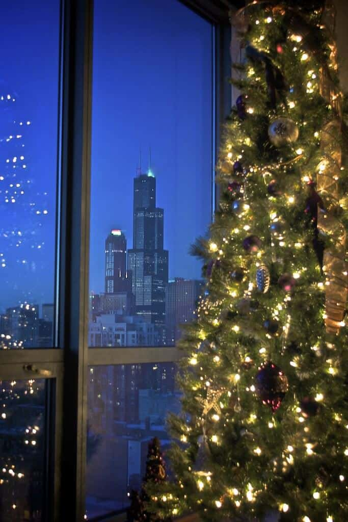 A Christmas tree next to an apartment window with a view overlooking a city.