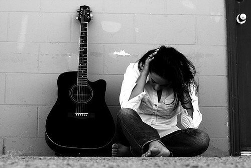 A black and white photo of a women with her head down next to a guitar on the ground.