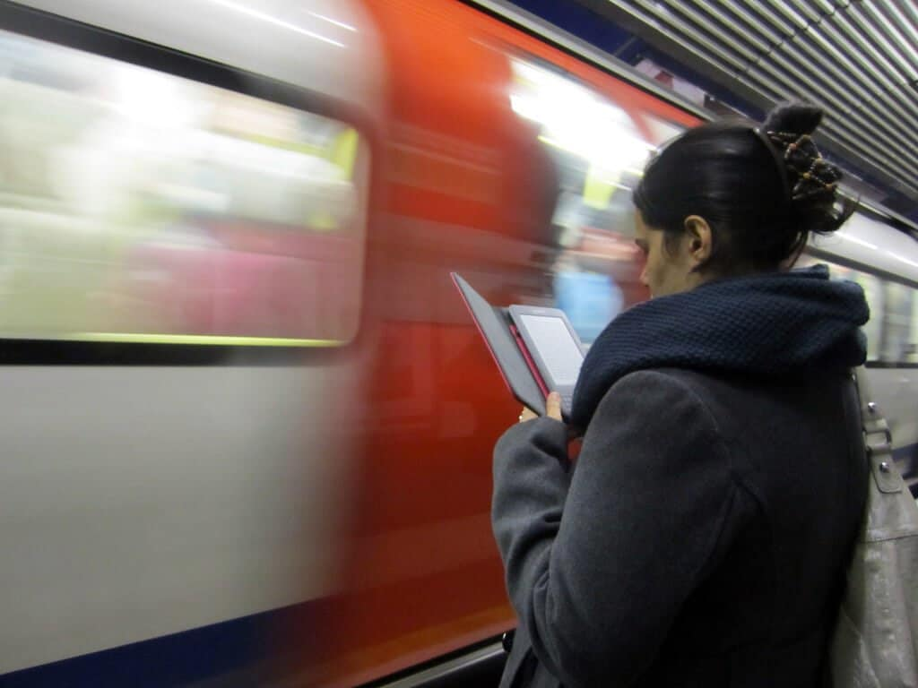 A women on a subway reading a book on a kindle.