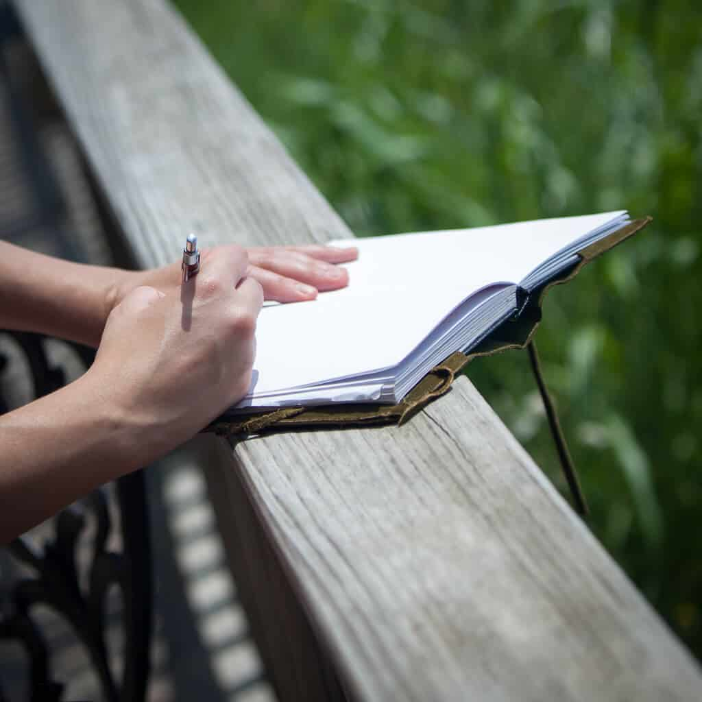 A closeup of someone writing in a journal.