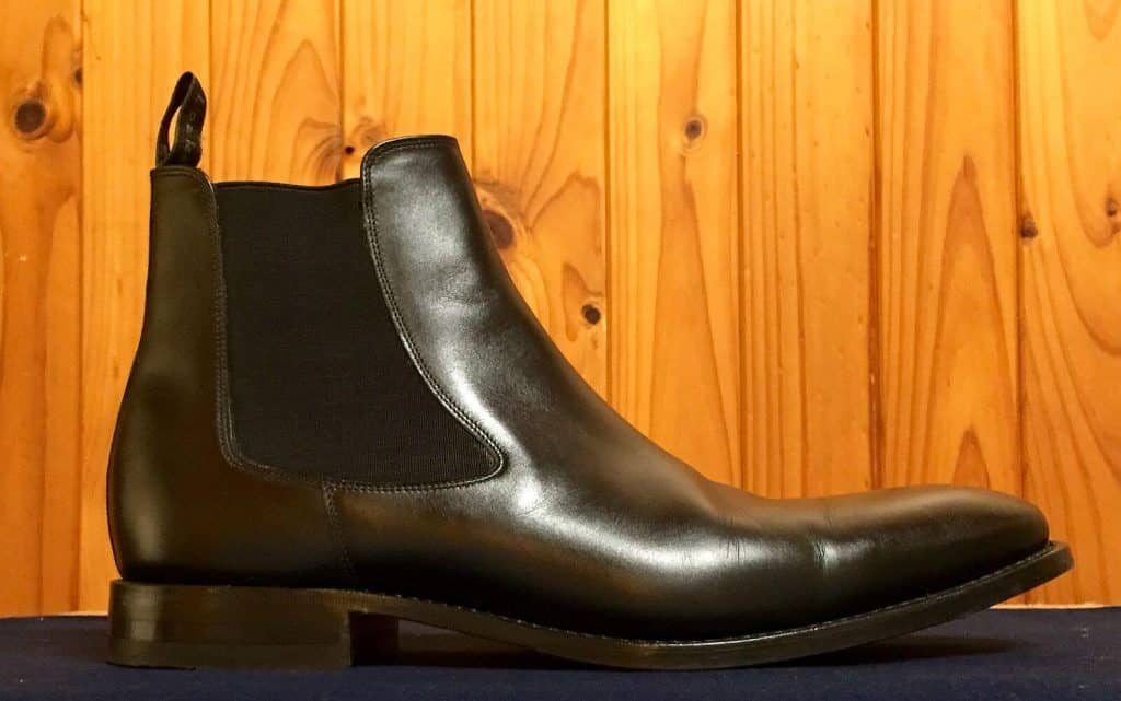 a black Chelsea Boot in front of a wooden wall