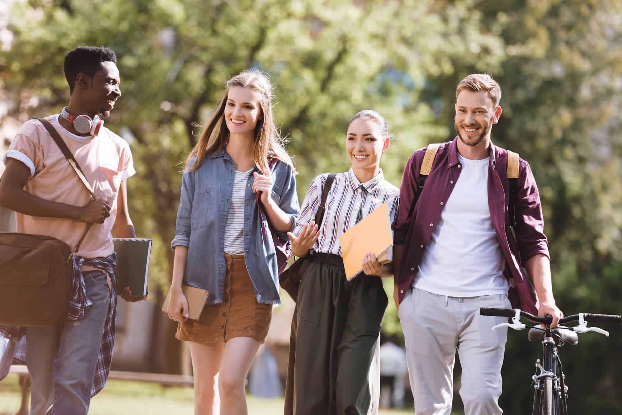 Four college students walking and smiling