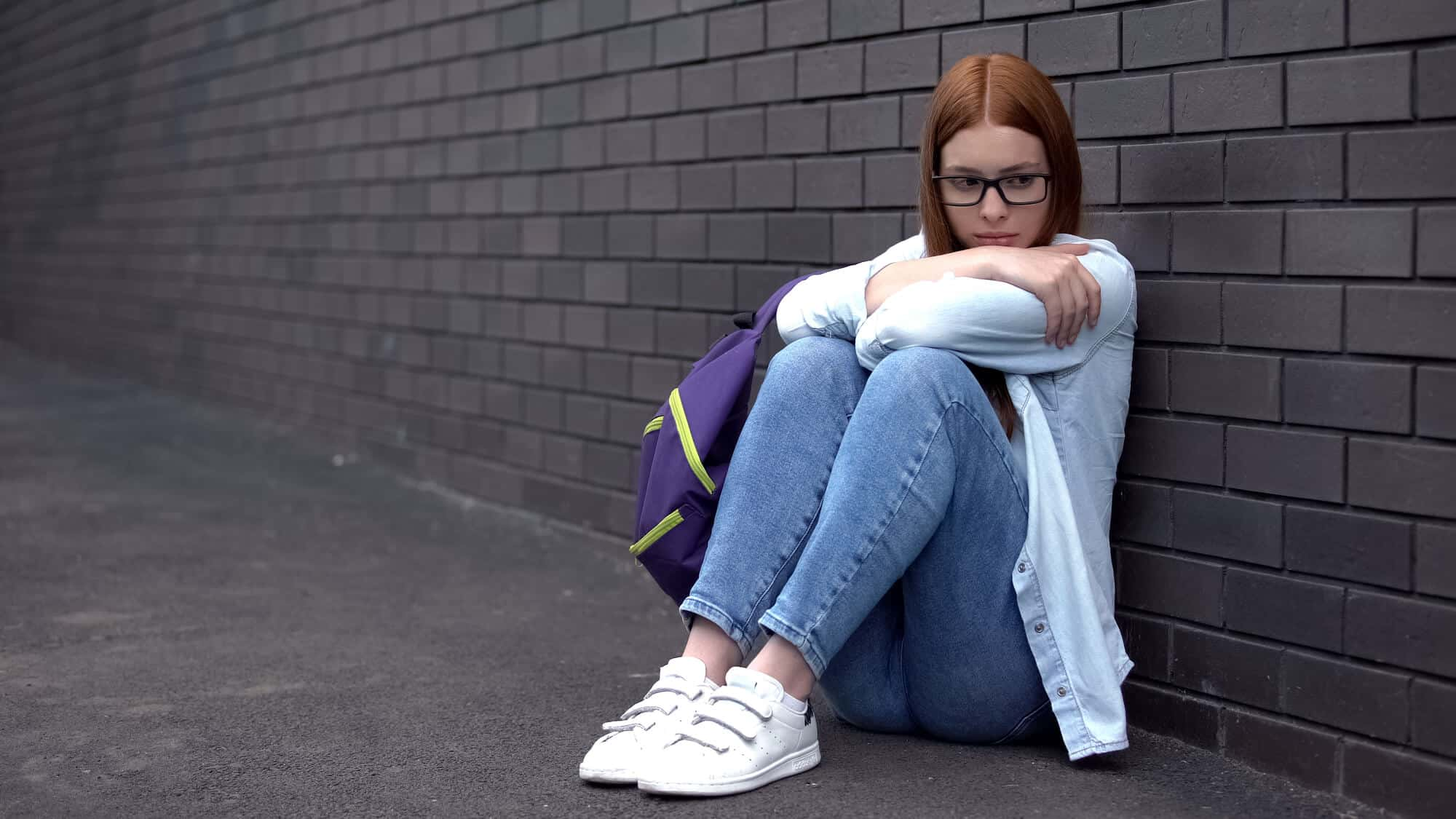 college students sitting on the ground holding her legs to her chest