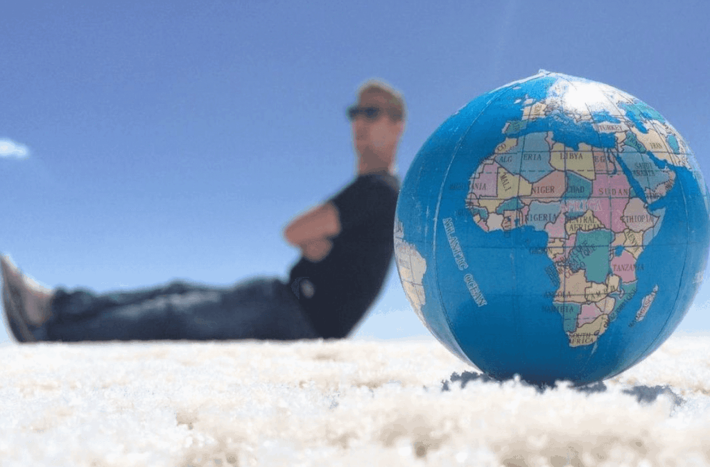 Johnny Ward leaning against a blow-up globe
