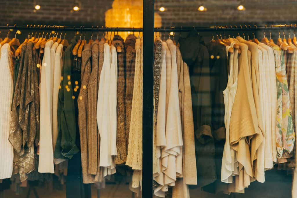 A clothing rack with about 30 sweaters of tan and brown tones