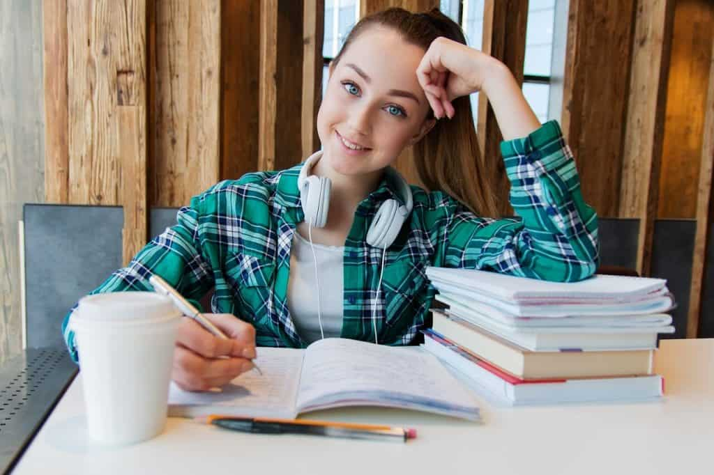 College student leaning on a stack of books on the table.