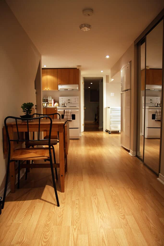 An apartment hallway with a chair and table set and stove in the back.