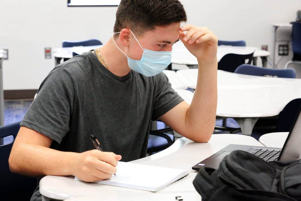 A student sitting at a table doing work on his laptop wearing a mask.