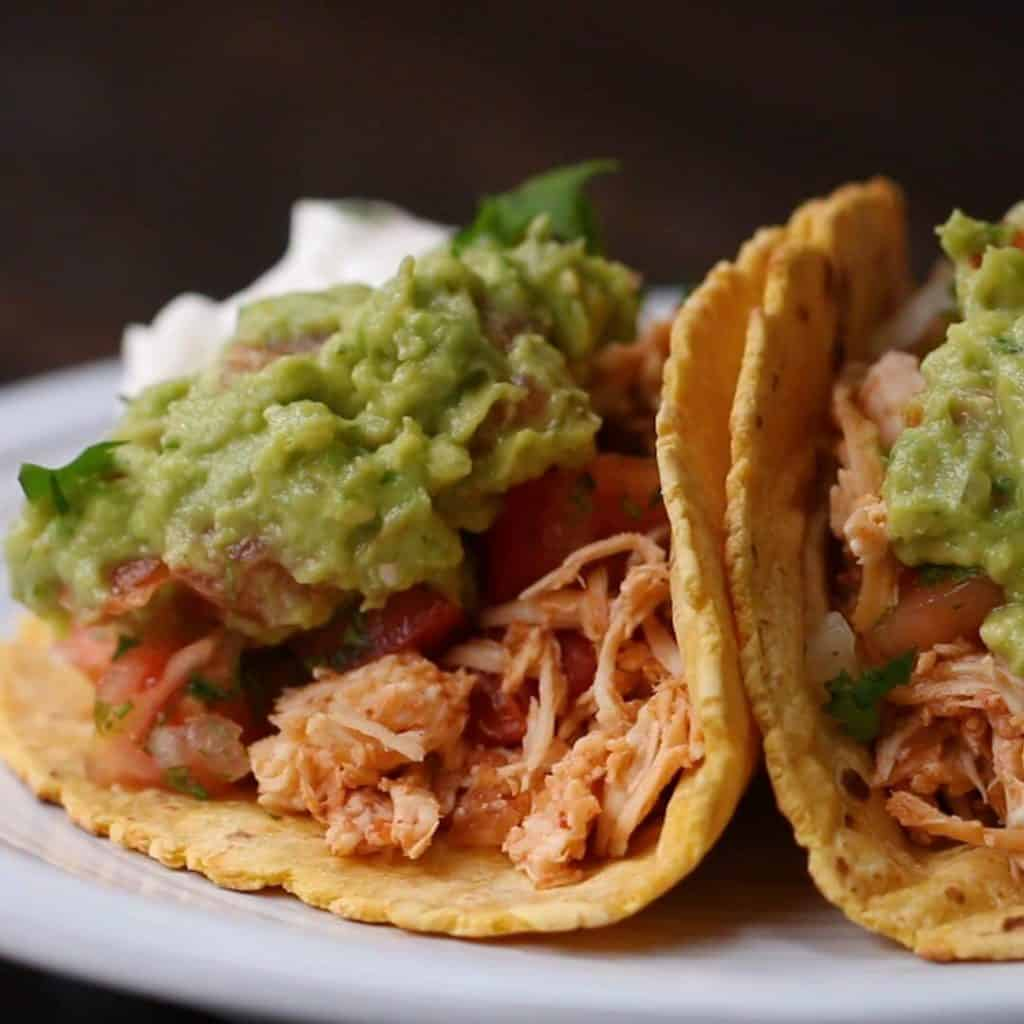 2 chicken tacos with tomatoes and guacamole sitting on a white plate