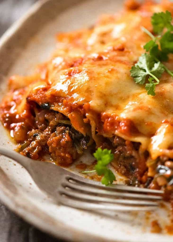 Spinach and beef cannelloni on a plate with a metal fork