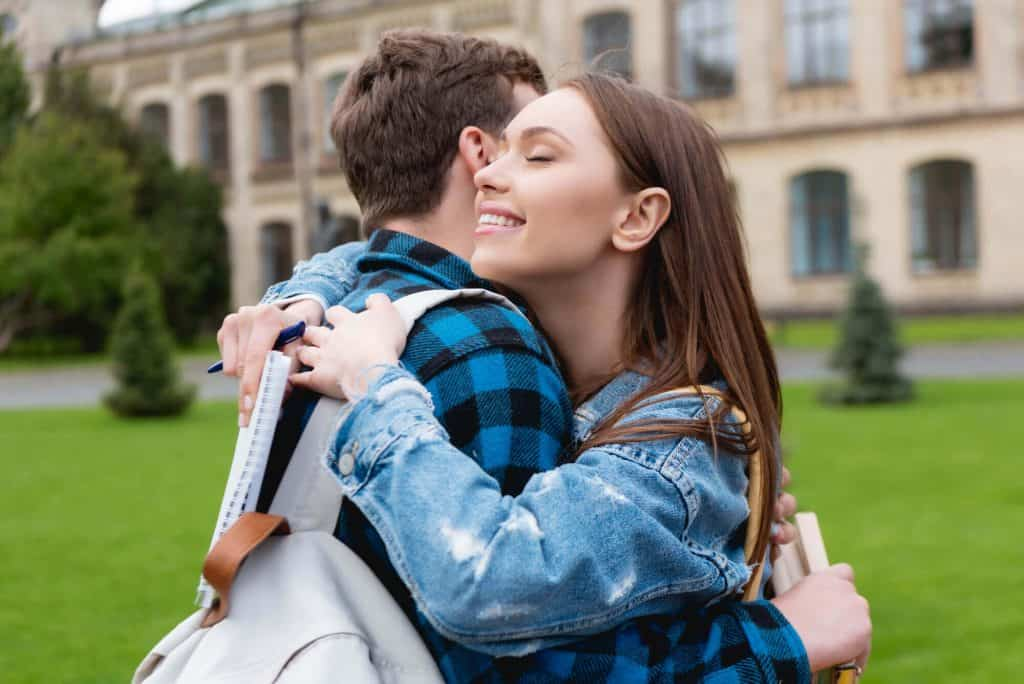 two college students are hugging each other