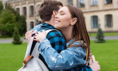 A beautiful college girl with long hair hugging her male college friend on campus