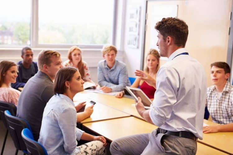 A professor speaking to students sitting around a table.