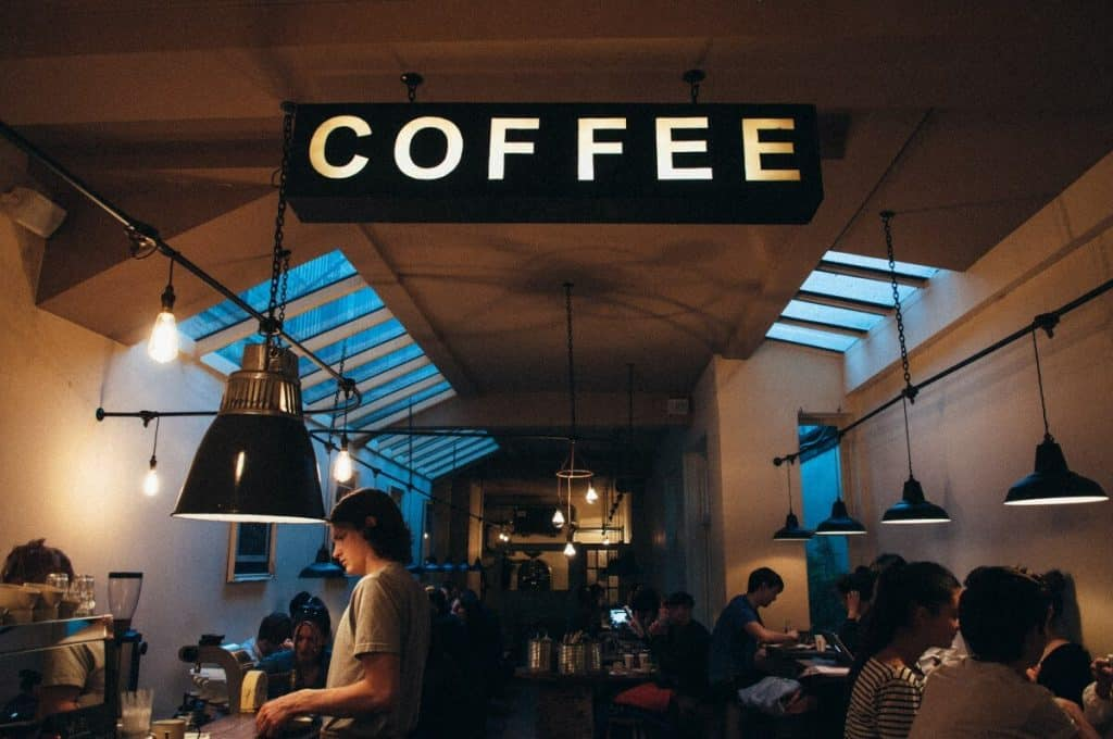 A busy coffee shop with a sign on the ceiling saying