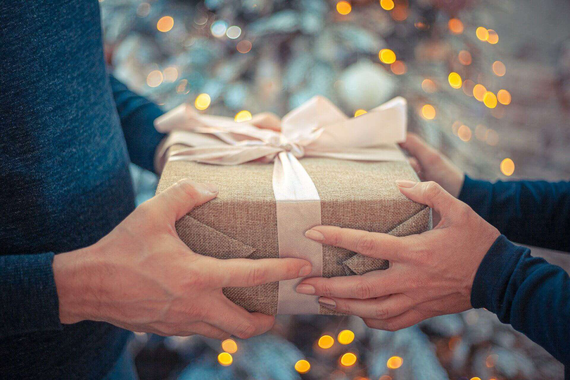 A woman is giving a brown gift box to a men