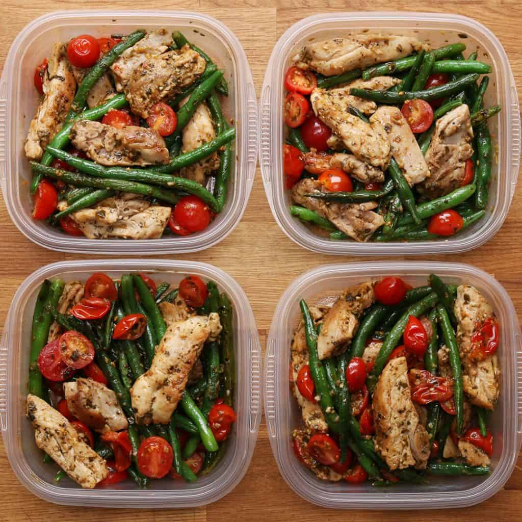 4 plastic containers with chicken, green beans, and tomatoes