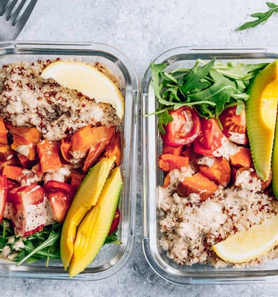 Two glass containers with rice and veggies and two forks at the top left corner.