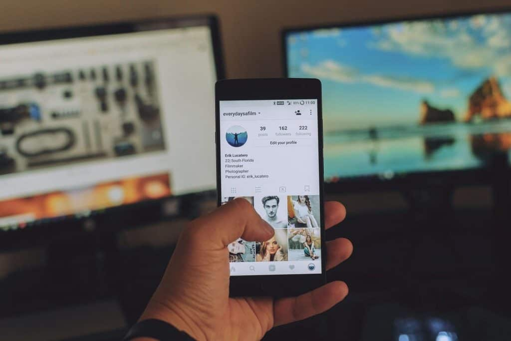 A left hand holding a cell phone with instagram on the screen