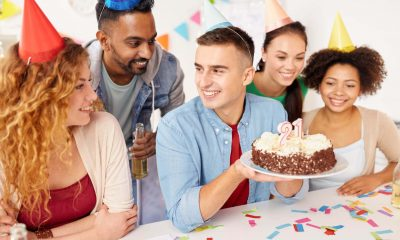 Five college students holding a cake and celebrating their friends 21st birthday.