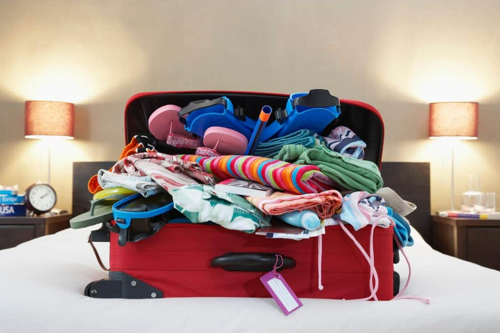 A overflowing red suitcase on a bed