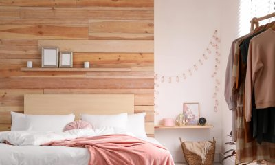 Bedroom with a wooden wall and white bedding and pink blanket