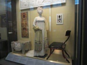 A mannequin wearing a Regency-era dress.