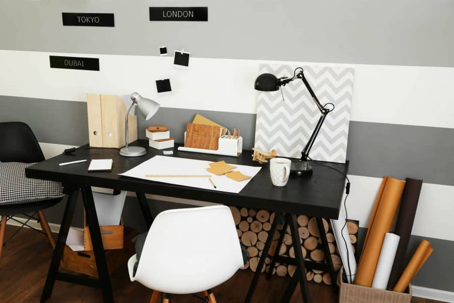 A black desk in a college dorm with various writing utensils and objects on it.
