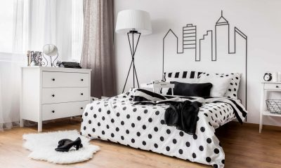 A room with white wall, standing lamp, cabinet, and a bed with black dot blanket