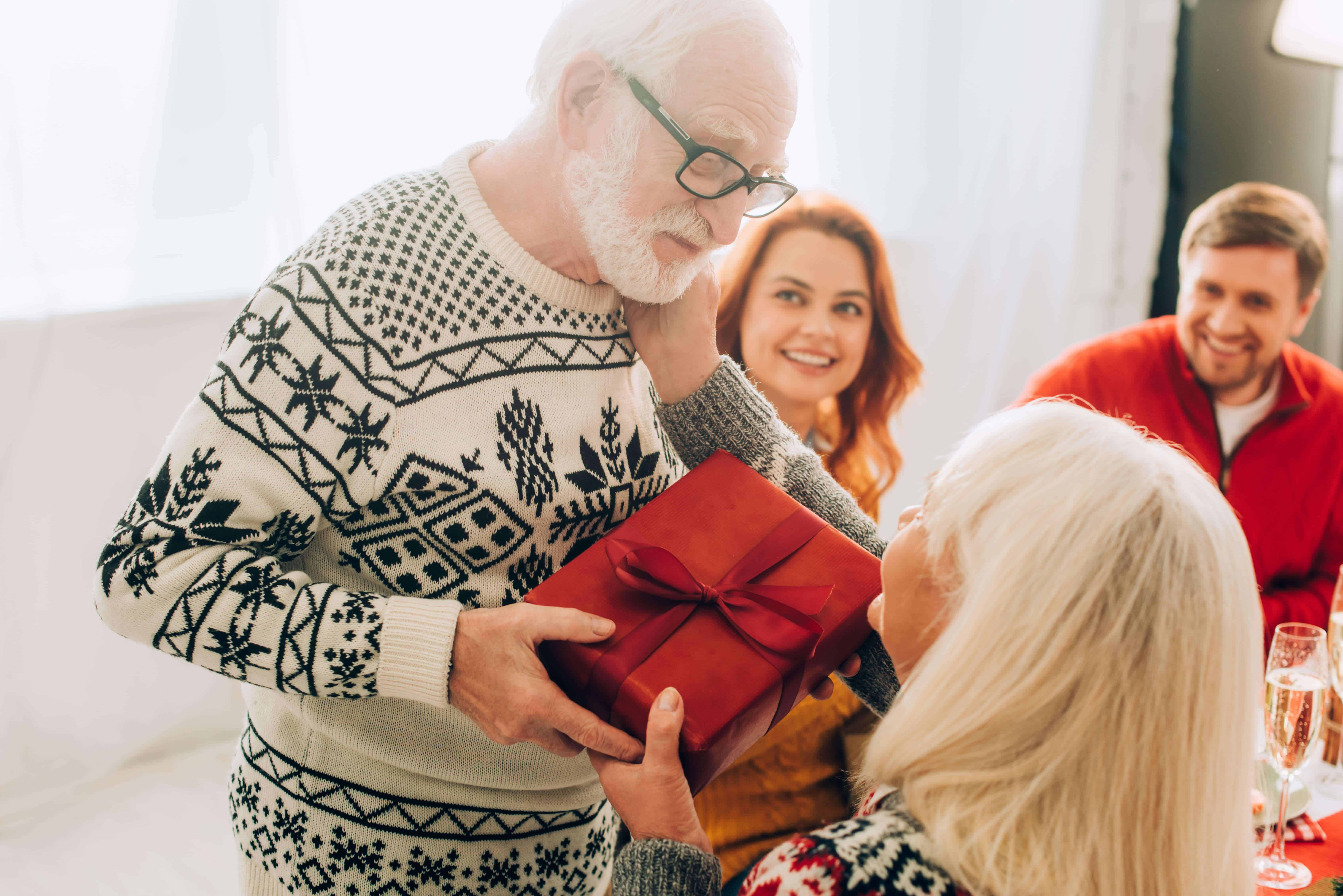 A grandpa is receiving gifts from his family