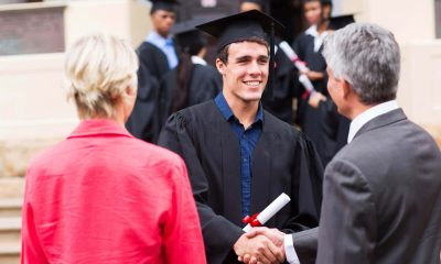 a graduate male student is talking to two people