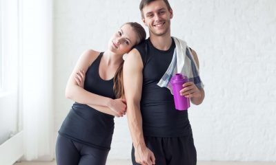 A couple wearing athletic clothes and smiling.