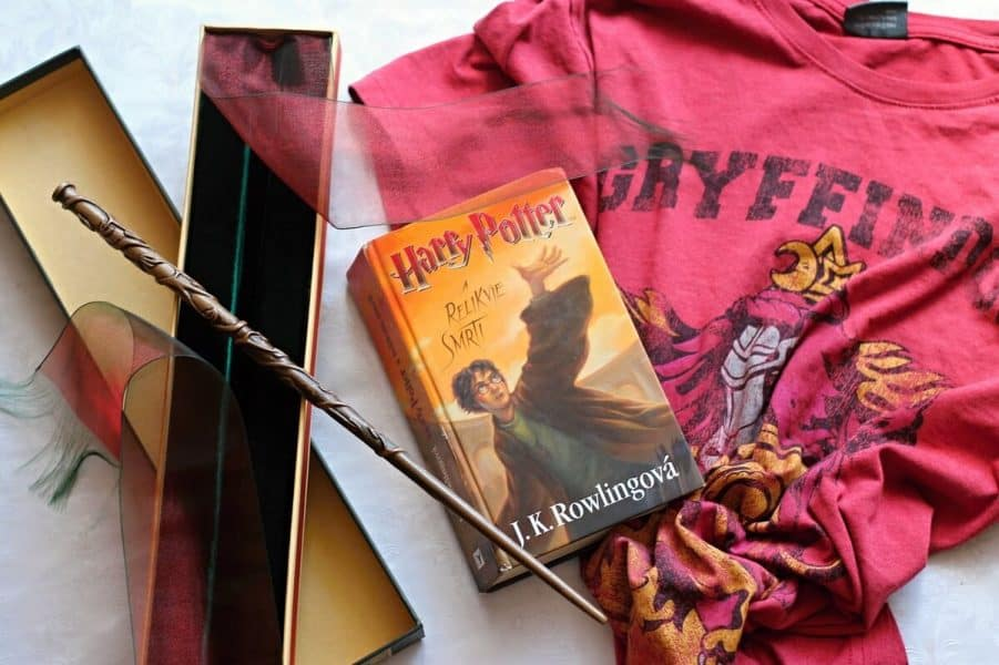 A picture of Harry Potter merchandise including a book, shirt and wand.