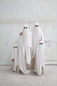 A family dressed as ghosts.