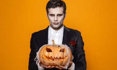 A man dressed as a vampire holding a jack-o-lantern.
