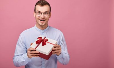 a man is holding a gift box