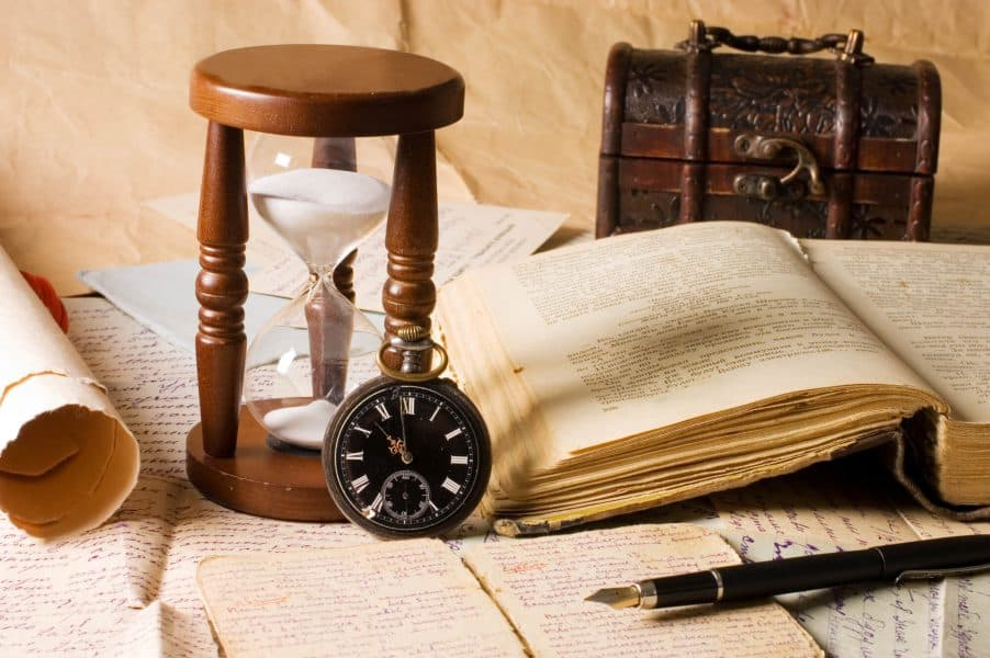 An hourglass on a table with various historical gifts.