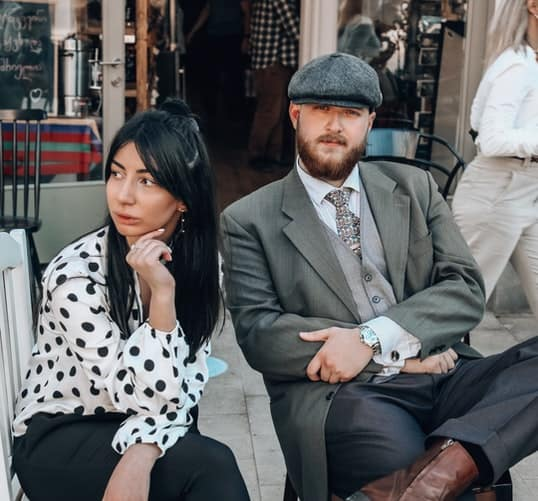 A well dressed couple sitting