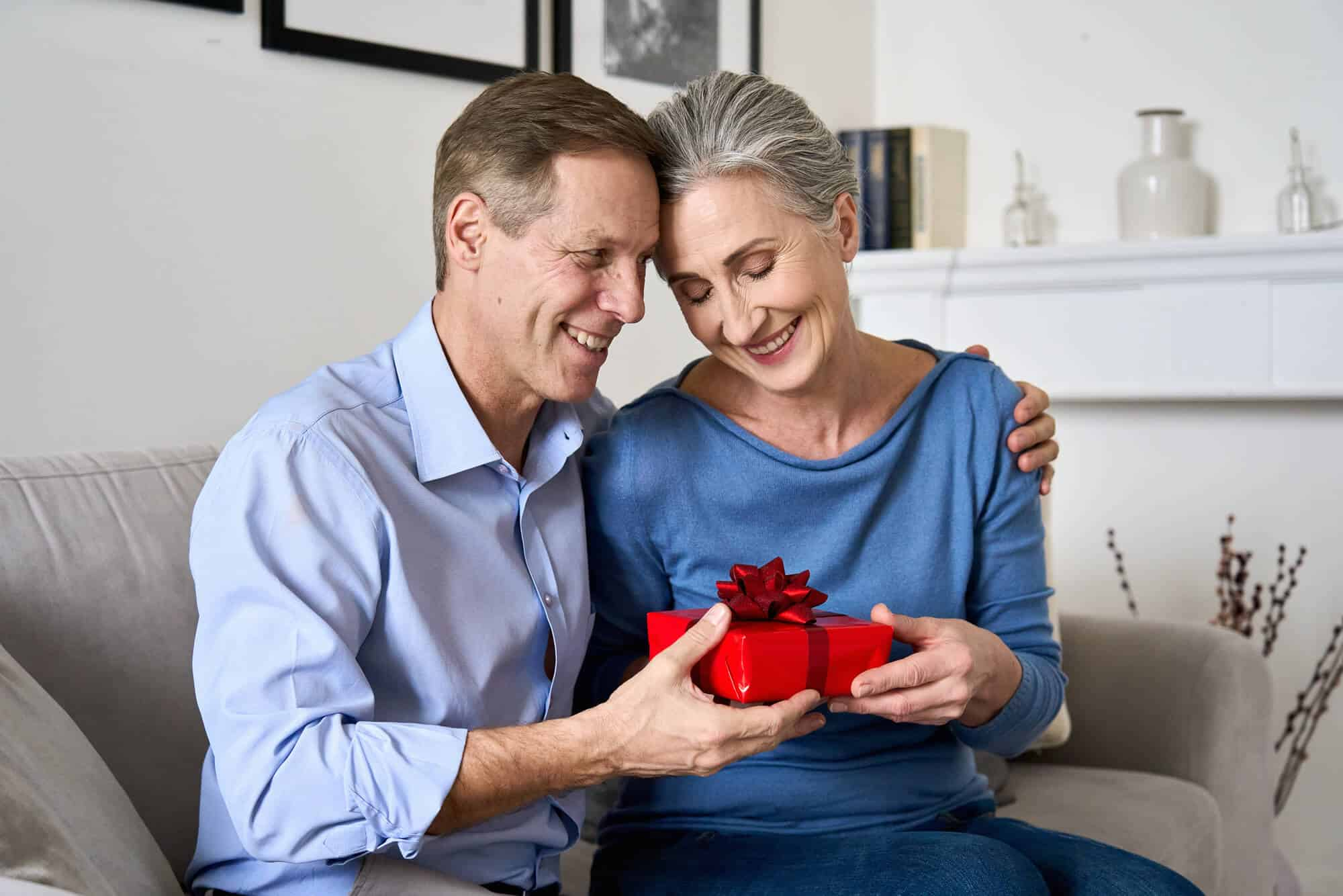 parents holding a red gift box and smiling