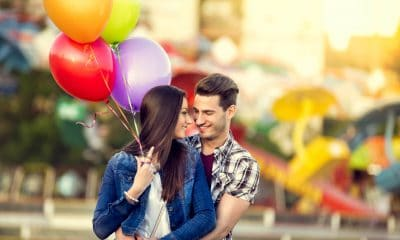A couple holding balloons