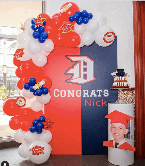A blue and red themed graduation decoration with balloons
