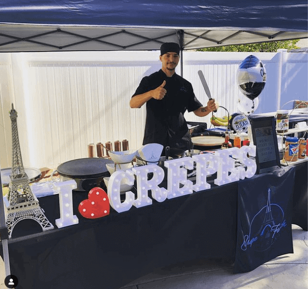 A man standing behind a crepe station
