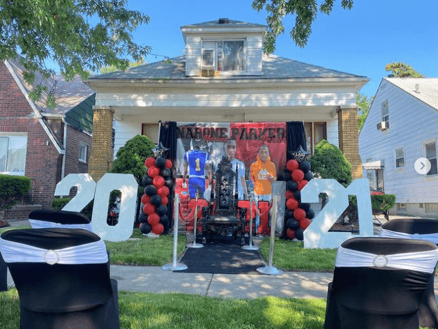 Graduation decoration in front of a house with balloons and a throne chair
