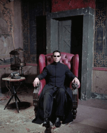 Neo from The Matrix seating on a chair