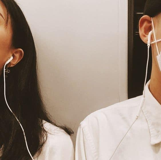 A boy and girl sharing an earphone