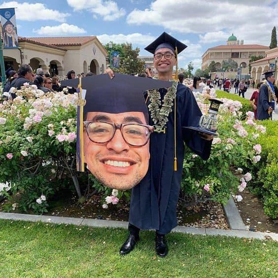 A grad holding a big head cutout of himself