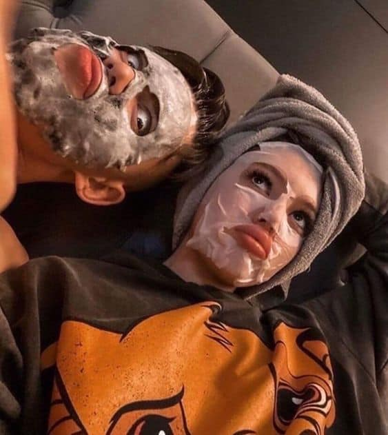 A couple making funny faces wearing facial masks
