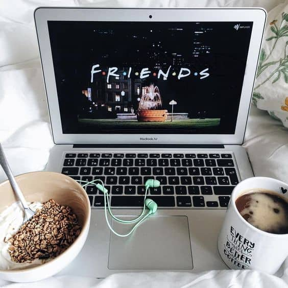 A laptop on a bed with a bowl of oatmeal and a cup of coffee