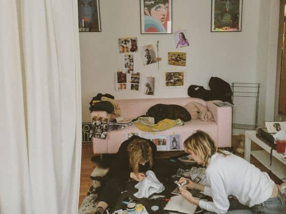 Two girls trying to finish a puzzle in a messy room
